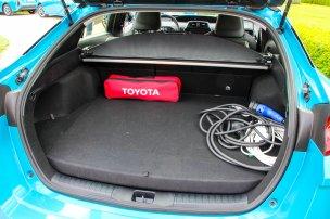 %KA%Hagyományos társánál jóval kisebb csomagtérrel szolgál a plug-in Prius, cserébe akkumulátora is nagyobb kapacitású. A töltő külön rekeszt kapott a magas padló alatt, az ajtó ugyanolyan büszkén mutatja szénszálas mivoltát, mint a BMW i3%KA%