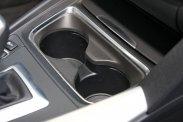 Ha elöl pohártartásra fognánk a váltó előtti teret, annak tálcája hely nélkül kallódik az utastérben; légbeömlő és nyitható pohártartó hátra is került